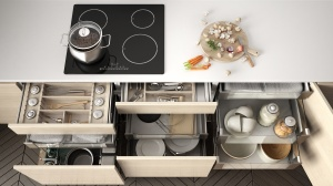 Opened wooden kitchen drawer with accessories inside, solution for kitchen storage and organizing, cooking, modern interior design
